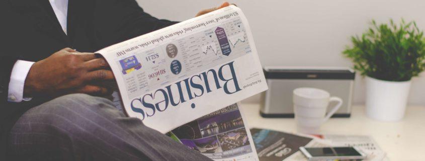 Mann im Anzug der ein Business-Magazin liest